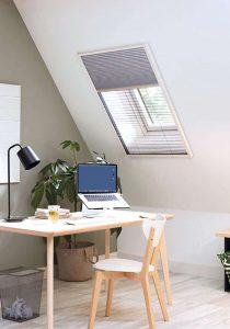 Skråvæg med vindue, hvor et DUO-plissé rullegardin er installeret, for både mørklægning og fluenet i ét